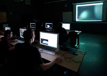 Students in dark room look at computer screens and big screen in front of room