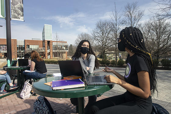 Students sit outside at a table at the Fairfax Campus